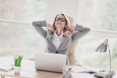 Incantando, bionda, donna graziosa che si siede allo scrittorio in posto di lavoro, HOL immagini stock libere da diritti