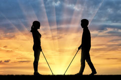 Incapacités d'hommes aveugles et de femmes avec le coucher du soleil de canne Photographie stock libre de droits