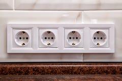 Incavi elettrici su una parete delle mattonelle della cucina fotografia stock libera da diritti