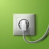 Incavo e spina bianchi elettrici realistici su verde Immagine Stock