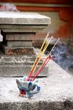 Incense. Burning incense on concrete wall, Bali royalty free stock image