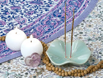 Incense. Sticks burning with candles, sandalwood prayer beads, heart shaped crystal, and 2 metal hearts on indian patterned cloth Royalty Free Stock Image