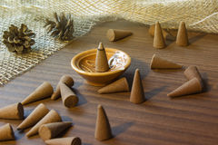 Incense aroma cones. In a stand on a wooden table. Aromatherapy theme background Royalty Free Stock Photo