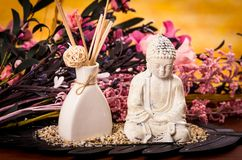 Incense and buddha statue with flowers spa concept Royalty Free Stock Image