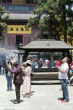 Incense burner at the Chan Buddhist Lingyin Temple. HANGZHOU, CHINA - MAY 4, 2015: Incense burner and people praying at the Lingyin Temple, a Buddhist temple of stock photos
