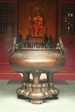 Incense Burner in a Chinese Temple. Joss stick prayer holder with kuan yin in the background royalty free stock photography