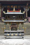 A incense burner in front of temple Stock Images