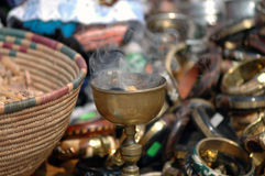 Incense Burning. Incense burns in a metal chalice at an outdoor African marketplace Stock Image