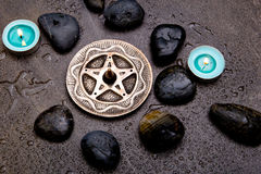 Incense burning in silver pentagram with blue candles and black. Rocks on gray slate background with water droplets royalty free stock photos