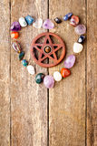 Incense burning in wooden pentagram burner with crystals in hear. T shape on wooden plank background royalty free stock photo