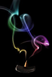 Incense cone with smoke. Colored smoke with incense cone over black Stock Photos