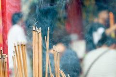 Incense el palillo de ídolo chino que quema lentamente con humo fragante del olor Gente que ruega en el templo budista chino en A Fotos de archivo