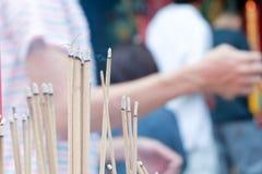 Incense el palillo de ídolo chino que quema lentamente con humo fragante del olor Gente que ruega en el templo budista chino en A Imagen de archivo