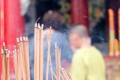 Incense el palillo de ídolo chino que quema lentamente con humo fragante del olor Gente que ruega en el templo budista chino en A Foto de archivo libre de regalías