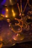 Incense en un soporte de oro de la forma y del oro lujoso s del símbolo de OM Imagenes de archivo