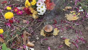 Incense on the grave. Smoldering incense on the grave and flowers stock video