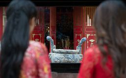 Incense ritual. Back view of two women looking at the urn with incense sticks Royalty Free Stock Photography