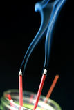 Incense smoke. Burning red incense sticks with smoke trails. Aromatic sticks when lighted also produce a pleasant odor. This rite could also be found in the Royalty Free Stock Image
