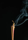 Incense smoke. Fired incense stick with smoke at black background Stock Photography