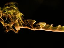 Incense smoke trails. Colorized incense smoke trails on a black background royalty free stock image