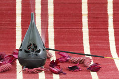 Incense stick. In burner with red flower leaves Royalty Free Stock Photos