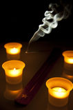 Incense stick and candles. Burning incense stick with lit candles and dark background Stock Photos