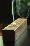 Incense stick smoking. In a wooden incense box Royalty Free Stock Images
