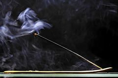 Incense stick smolders and emits intensive smoke Royalty Free Stock Image