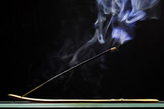 Incense stick smolders and emits intensive smoke Royalty Free Stock Photography