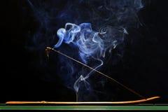 Incense stick smolders and emits intensive smoke Stock Photo