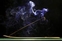 Incense stick smolders and emits intensive smoke Stock Image