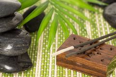 Incense sticks with black basalt stones  and green leaf, on bamboo mat Stock Images