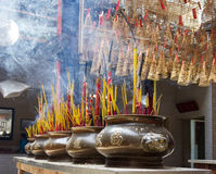 Incense sticks in a Buddhist Temple in Vietnam. Incense sticks in metal pots and on the rooftop in a buddhist temple in Vietnam royalty free stock images