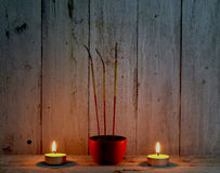 Incense sticks with candle flame on wooden background Stock Photo