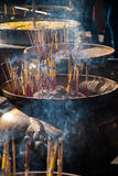 Incense sticks and smoke in ashes bucket Royalty Free Stock Image