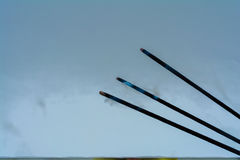 Incense sticks. Three incense sticks smoldering on blue background Royalty Free Stock Images