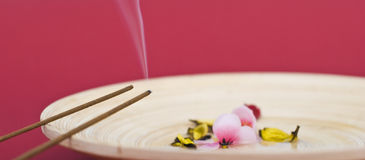 Incense sticks on wooden plate. Zen decoration from 2 incense sticks on wooden plate with flower arrangement inside Royalty Free Stock Photography