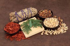 Incense Types. Frankincense, myrrh, sandalwood, incense cones , cedar leaf and smudge stick over lokta paper background stock photos