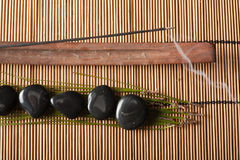 Incense and volcanic hot-stones. Burning incense and volcanic hot-stones placed on bamboo mat Stock Photography