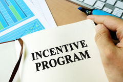 Incentive program. Hands holding book with title Incentive program Royalty Free Stock Photos