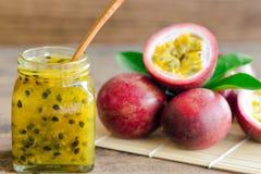 Inceppamento delizioso casalingo del frutto della passione in bottiglia messa sulla tavola di legno Immagine Stock