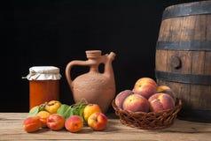 Inceppamento dell'albicocca dentro dei barattoli di vetro e della frutta fresca Fotografia Stock