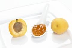 Inceppamento dell'albicocca, un'albicocca e una metà su un piatto del wite Fotografia Stock