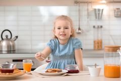 Inceppamento di diffusione della bambina sveglia su pane tostato saporito Fotografia Stock