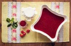 Inceppamento di fragola casalingo (marmelade) in barattoli su fondo di legno Fotografia Stock