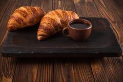 Inceppamento di recente al forno del croissant, tazza di caffè in tazza bianca su fondo di legno marrone Pasticcerie fresche dell fotografie stock libere da diritti