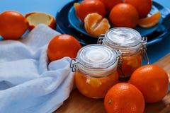 Inceppamento dolce dalle arance in piccoli barattoli con le arance fresche Immagine Stock