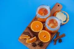Inceppamento dolce dalle arance in piccoli barattoli con le arance, la cannella e il anice cutted freschi sulla tavola blu Immagine Stock Libera da Diritti