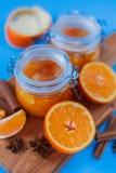 Inceppamento dolce dalle arance in piccoli barattoli con le arance, la cannella e il anice cutted freschi sulla tavola blu Immagini Stock