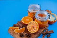 Inceppamento dolce dalle arance in piccoli barattoli con le arance, la cannella e il anice cutted freschi sulla tavola blu Fotografie Stock Libere da Diritti